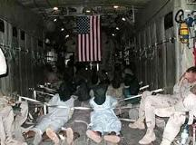 Detainees with U.S. flag hanging above them