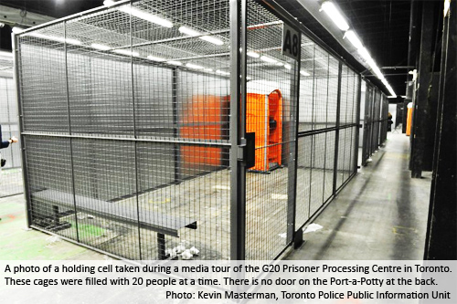 A photo of a holding cell taken during a media tour of the G20 Prisoner Processing Centre in Toronto. These cages were filled with 20 people at a time. There is no door on the Port-a-Potty at the back. Photo: Kevin Masterman, Toronto Police Public Information Unit.
