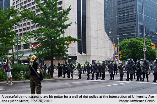 A peaceful demonstrator plays his guitar for a wall of riot police at the intersection of University Ave and Queen Street, June 26, 2010. Photo: Lawrence Gridin.