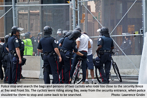 Police stop and search the bags and persons of two cyclists who rode too close to the security fence at Bay and Front Sts. The cyclists were riding along Bay, away from the security entrance, when police shouted for them to stop and come back to be searched. Photo: Lawrence Gridin.